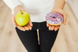 Diet. Woman Measuring Body Weight On Weighing Scale Holding Donut and apple. Sweets Are Unhealthy Junk Food. Dieting, Healthy Eating, Lifestyle. Weight Loss. Obesity