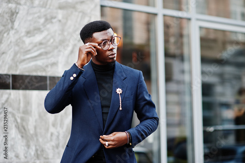 Fotomural  Amazingly looking african american man wear at blue blazer with brooch, black turtleneck and glasses posed at street