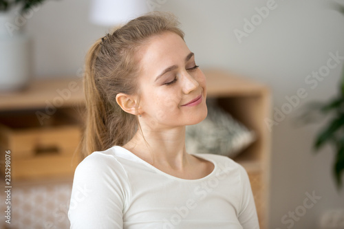 Cuadros en Lienzo Close up of happy young woman sitting with eyes closed dreaming at home, smiling