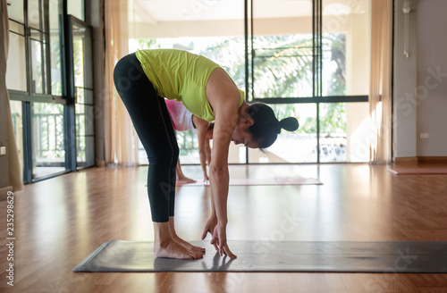 Couple of yogis in uttanasana  Young woman practicing