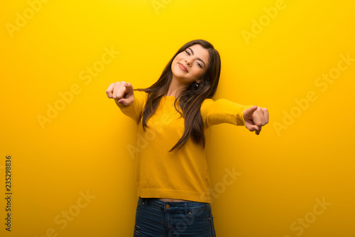 Pinturas sobre lienzo  Teenager girl on vibrant yellow background points finger at you while smiling