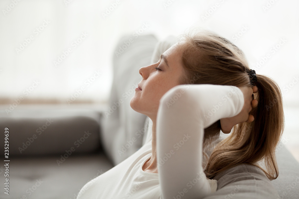 Fototapeta Close up of calm young female relax on cozy couch with eyes closed, peaceful girl lying on sofa hands over head having rest at home, dreamy woman stretching enjoying weekend morning in apartment
