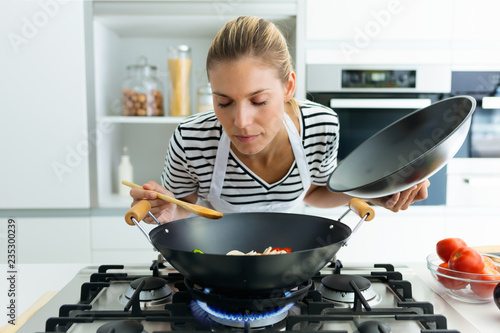 Fotografie, Obraz  Healthy young woman cooking and smelling food in frying pan in the kitchen at home