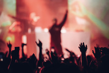 Silhouette Of A Singer On A Stage Singing To The Crowd With The Hands Raised Up
