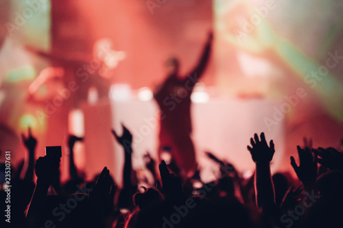Fotografiet  Silhouette of a singer on a stage singing to the crowd with the hands raised up
