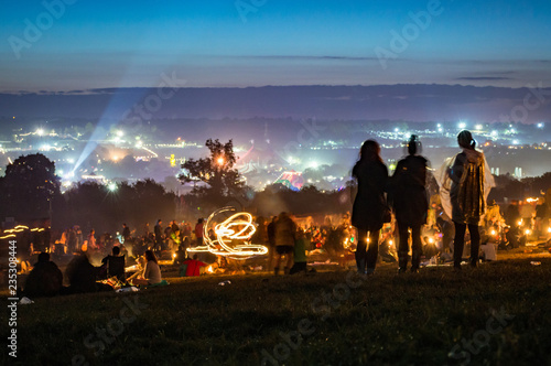 Three girls silhouetted before sunrise, looking out over the lights, fires and lasers of Glastonbury Festival.. UK.