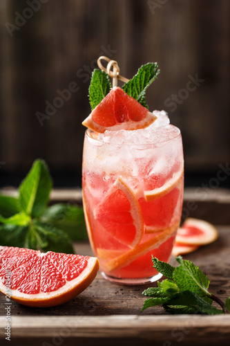 Fresh grapefruit cocktail. Fresh summer cocktail with grapefruit and ice cubes. Glass of grapefruit mojito