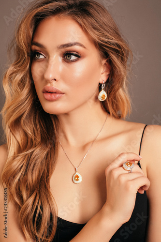 Slika na platnu beautiful woman with blond curly hair in elegant dress and jewelry accessories