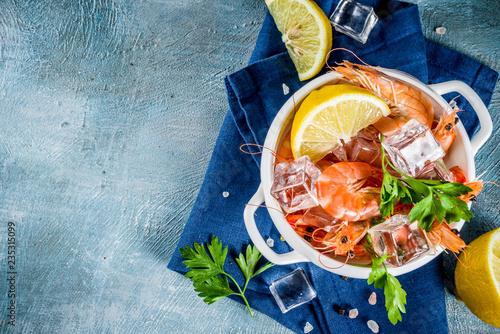 Owoce morza, gotowane krewetki z cytryną i lodem na jasnoniebieskim tle