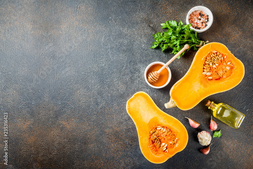 Fotografía  Halves of raw pumpkin or butternut squash, with olive oil, spices and ingredients for cooking on dark background