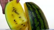 A man's hand takes half of a yellow watermelon
