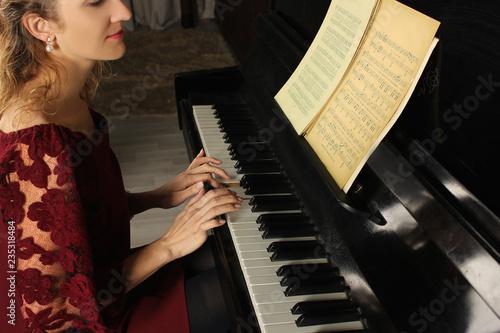 Foto op Canvas Muziekwinkel Young beautiful woman playing on the black piano closeup
