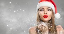 Christmas Winter Fashion Girl On Holiday Blurred Winter Background. Beautiful New Year And Xmas Holiday Makeup. Beauty Model Woman In Santa's Hat Blowing Snow In Her Hand