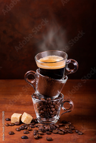 Photo  glass cups, in sequence vertically, with coffee beans, ground, and steaming drink
