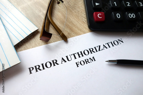 Fotografia, Obraz Prior authorization form with pen, calculator and   glasses on desk