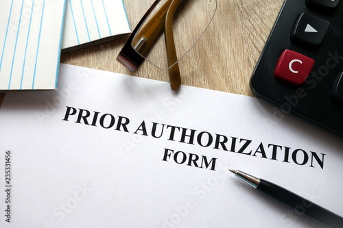Fototapeta Prior authorization form with pen, calculator and   glasses on desk