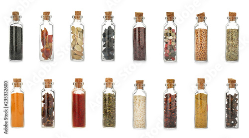 Glass bottles with different spices and herbs on white background. Large collection