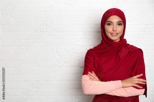 Portrait of young Muslim woman in hijab against brick wall. Space for text