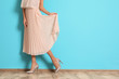 canvas print picture - Young woman with beautiful long legs in stylish outfit near color wall, closeup. Space for text