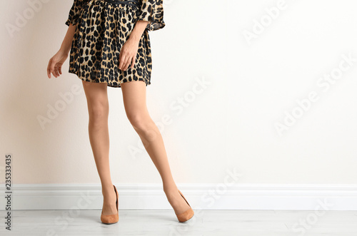 Young woman with beautiful long legs in stylish outfit near white wall, closeup. Space for text