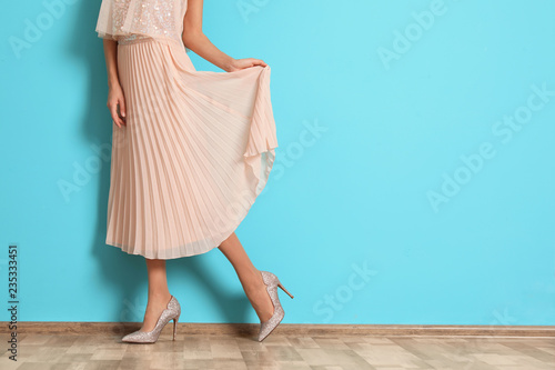 Young woman with beautiful long legs in stylish outfit near color wall, closeup. Space for text