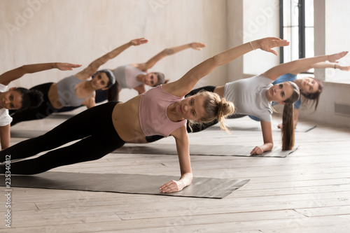 Group of young diverse sporty people doing yoga Vasisthasana pose, Side Plank exercise, working out, indoor close up, female students training at sport club or studio Fototapeta