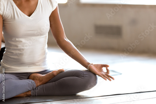 Young black yogi woman practicing yoga, doing Ardha Padmasana exercise, Half Lotus pose with mudra gesture, working out, wearing sportswear, indoor close up, yoga studio. Well being, wellness concept