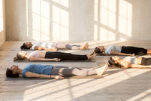 Group Of Young Attractive People Practicing Yoga Lesson Doing Dead Body, Savasana Exercise, Corpse Pose, Working Out, Indoor Full Length, Mixed Race Female Students Training At Club Or Yoga Studio