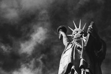 Statue Of Liberty At Isle Of The Swans In Paris (France) Against Sky With Clouds At Background. Closeup. Bottom View. Black And White Photo.
