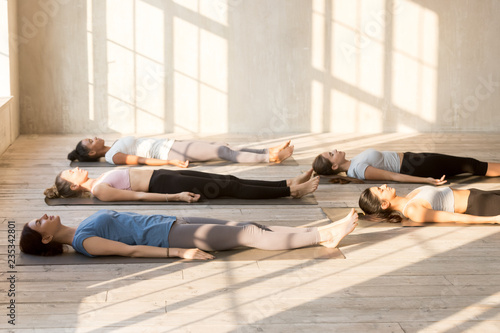 Photo Group of young attractive people practicing yoga lesson doing Dead Body, Savasan