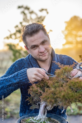 Bonsai artist pruning bonsai tree outdoors