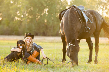 Girl horse rider sitting with a dog near the horse and hugs the horse. Horse theme