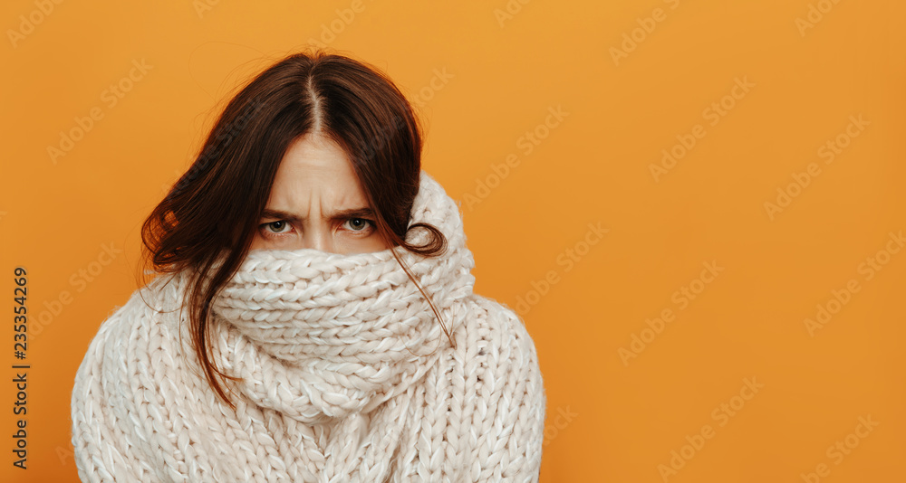 Fototapety, obrazy: Cough and cold. Health. Woman portrait. Girl is looking from under her knitted scarf, on an orange background