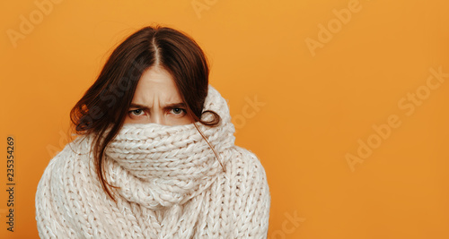 Obraz Cough and cold. Health. Woman portrait. Girl is looking from under her knitted scarf, on an orange background - fototapety do salonu
