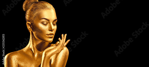 Golden skin woman portrait closeup. Sexy model girl with holiday golden shiny professional makeup. Golden metallic body