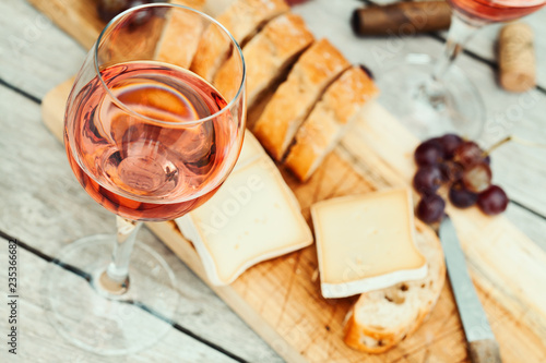 Two glasses of rose wine and board with fruits, bread and cheese on wooden table Fotobehang