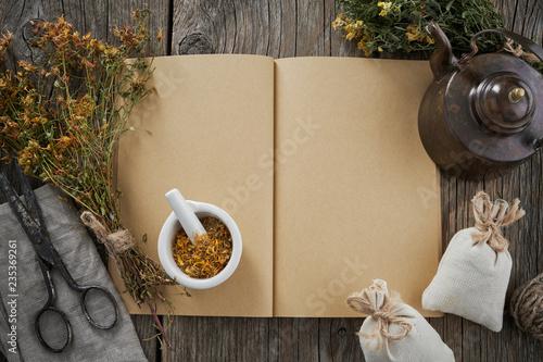 Open medical recipe book; Hypericum - St Johns wort bunch; mortar and vintage teapot Canvas Print
