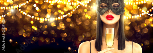 Spoed Fotobehang Carnaval Christmas and New Year holiday celebration. Beauty glamour woman celebrating with champagne, wearing carnival mask, drinking sparkling wine over holiday glowing background. Widescreen