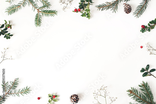 Obraz Christmas floral frame, decorative border. Winter composition of red cranberry branches, baby's breath flowers, spruce tree branches and larch cones on white table. Festive background. Flat lay, top - fototapety do salonu