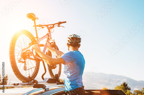 Fotografía  Mountain biker man take of his bike from the car roof evening sunset image