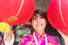 Happy Smile Women Wear Cheongsam Red Dress Standing Between The Red Lantern In Her Hand, On Chinese Atmosphere Background. People, Beauty And Ethnicity Concept.