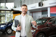 Salesman with clipboard and car keys in modern auto dealership