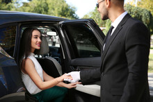 Driver Opening Car Door For Young Businesswoman. Chauffeur Service