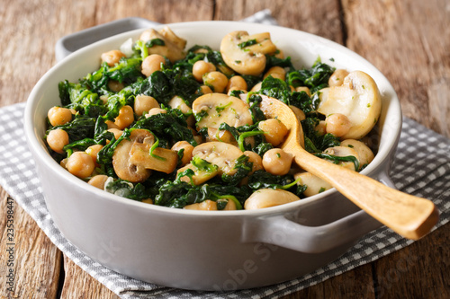 Cooked diet chickpeas with spinach and champignons close-up in a bowl. horizontal