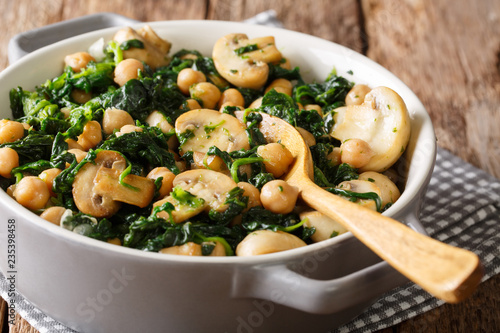 Healthy vegetarian food of chickpeas with spinach and mushrooms close-up in a bowl. horizontal