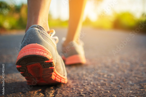 Feet of woman walking and exercise on the road during sunset.