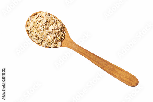 Fotografía  Uncooked oatmeal in  wooden  spoon isolated on white top view