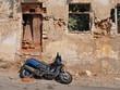 Blauer Motorroller vor zerfallener Fassade