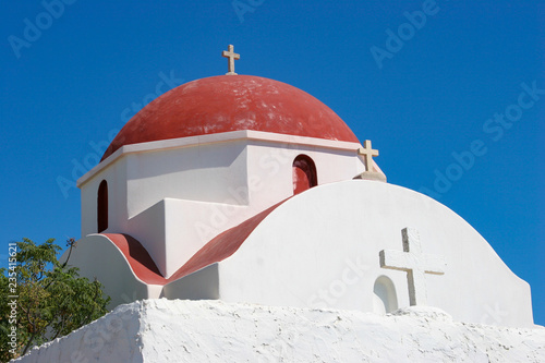 Fotografie, Obraz  White Church with a Red Dome set against the beautiful blue skies of Mykonos, Gr