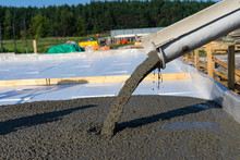 Workers Pour The Foundation For The Construction Of A Residential Building Using Mobile Concrete Mixers.